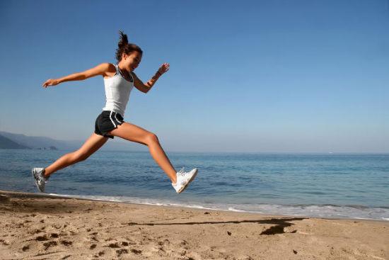 Fitness: donna che fa una corsa sulla spiaggia
